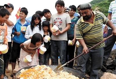 阿里木为受灾群众做手抓饭.图片