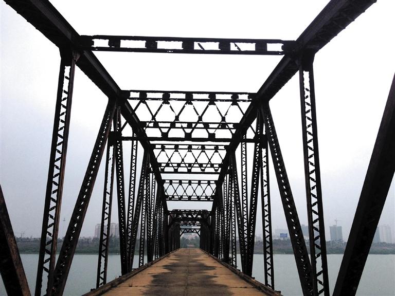 -->  距离南渡江出海口约7公里,站在新大洲大桥上往北看,您能轻易看见一座残存的桥梁。桥梁东边已经垮塌,仅剩下歪歪斜斜的桥墩立在水中;桥梁西侧的桥体依然完好,屹立水中,透出历史的芬芳。   这就是有名的南渡江铁桥。几乎每个海口人都知道。可却少有人知道,这桥原由日本人修建,原名吕宫桥,曾被海口人叫做鬼子桥,视作鬼门关。   本报记者 敖坤 文/图   A 曾经的海南第一桥   南渡江铁桥,在海口是一个响亮的名字。   在滨江路这边往东看,可看到散落的桥墩。四个桥墩歪歪斜斜倒在水中。桥墩对