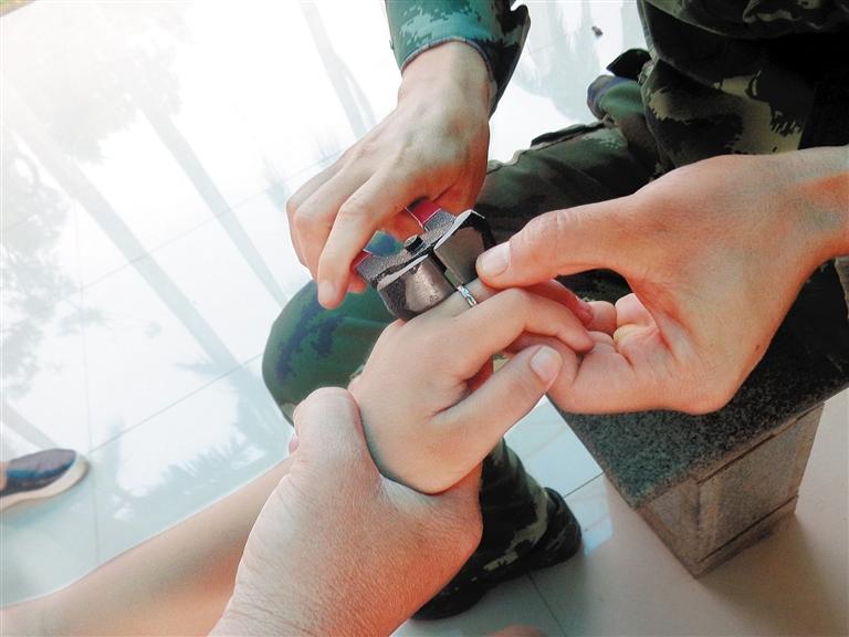 -->  南国都市报8月14日讯(记者 何慧蓉 通讯员 逢宇 文/图)12日下午5点半左右,一个中年女子骑着电动车,将一个六七岁的小男孩带到了临高消防中队。小男孩的左手中指上卡着一个银戒指,手指有些红肿。   该女子介绍,小男孩是她的儿子,因为觉得好玩,孩子偷偷将她的戒指(尾戒)戴在手上,结果摘不下来了。5天来,戒指一直卡在孩子的手指上,家人多次尝试取下来,都没有成功,结果孩子的手指出现了红肿。因此,她才带孩子来到消防中队求助。消防官兵仔细观察后,马上找来钳子等破拆工具。经过1分钟细心剪切,戒指被剪断并