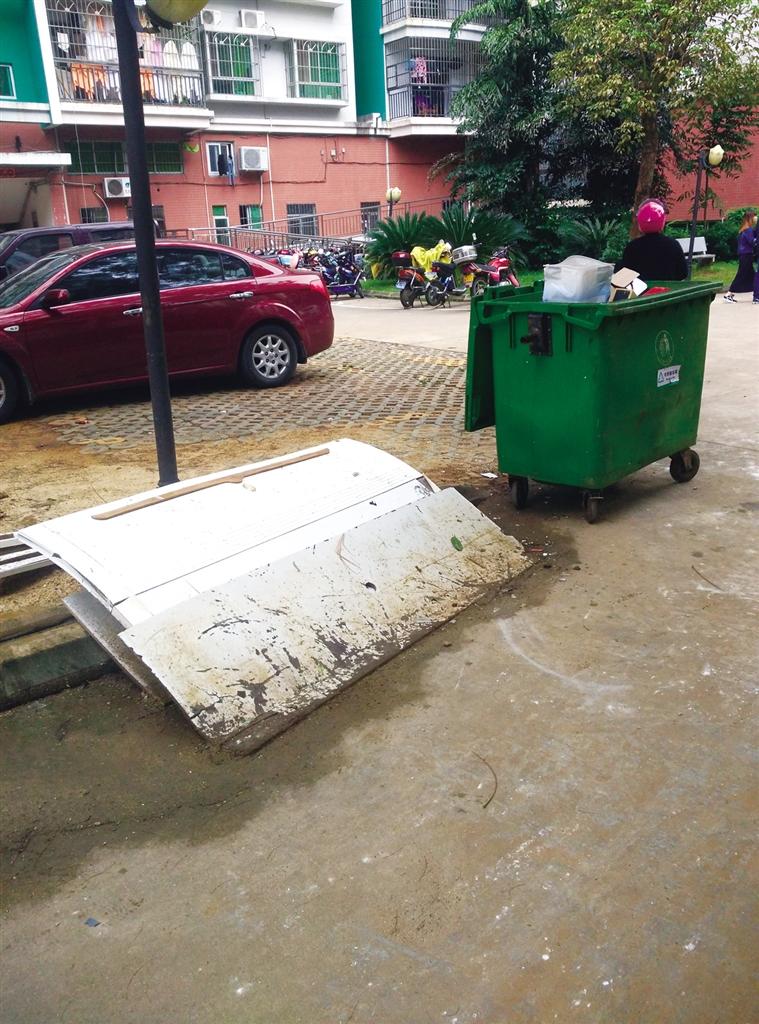 被丢弃在垃圾桶旁边的白色破旧木床